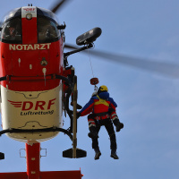 An einem Hubschrauber der DRF Luftrettung hängen zwei Personen an der Rettungswinde.