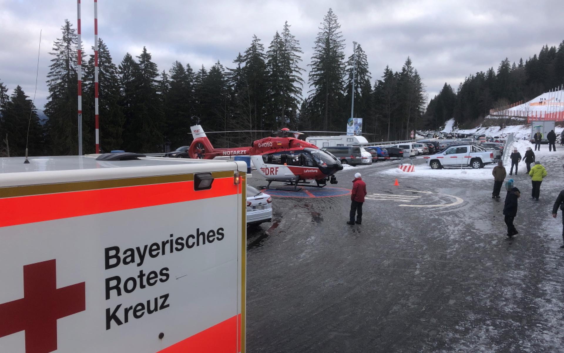 Rettungshubschrauber Christoph Regensburg steht auf dem Parkplatz an der Talstation eines Skilifts.