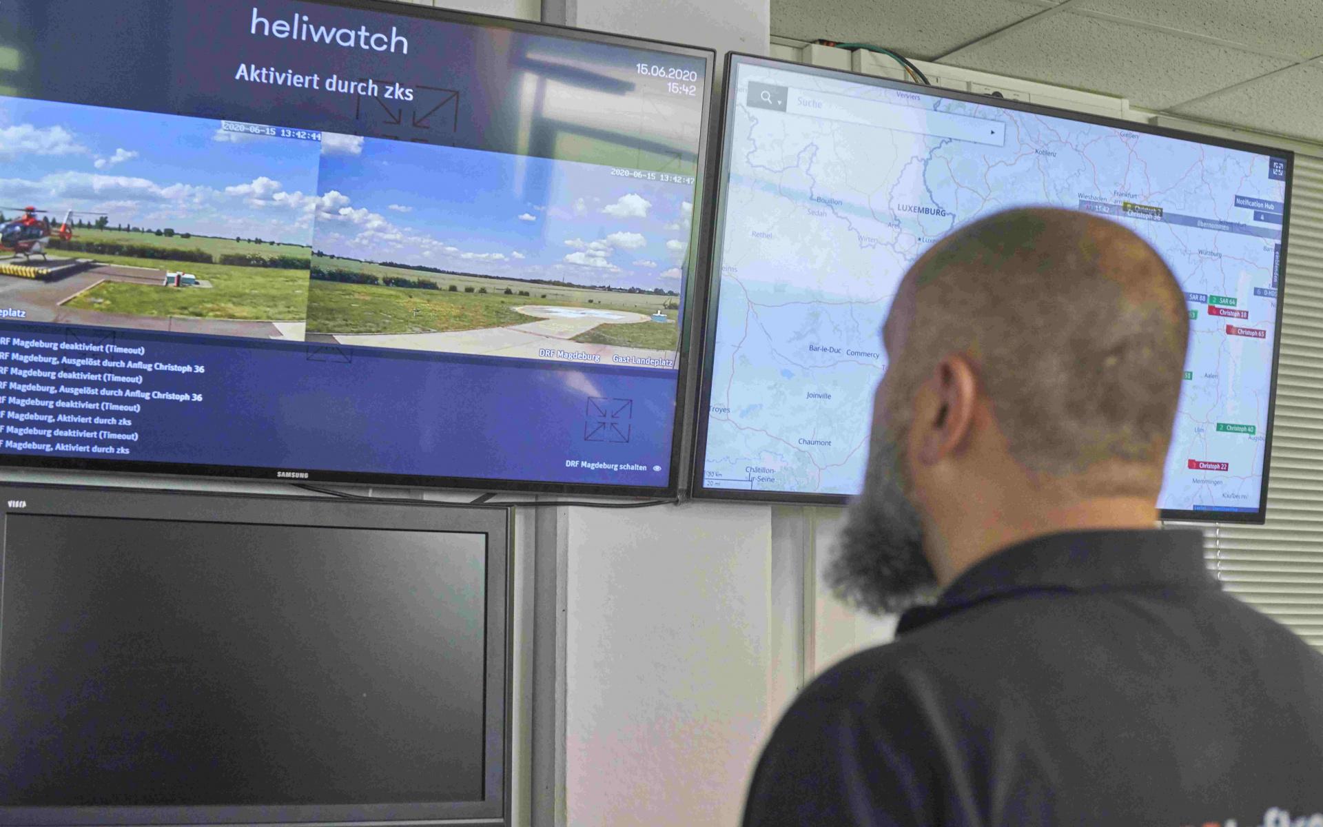 Ein Mann schaut auf zwei Bildschirme an der Wand.