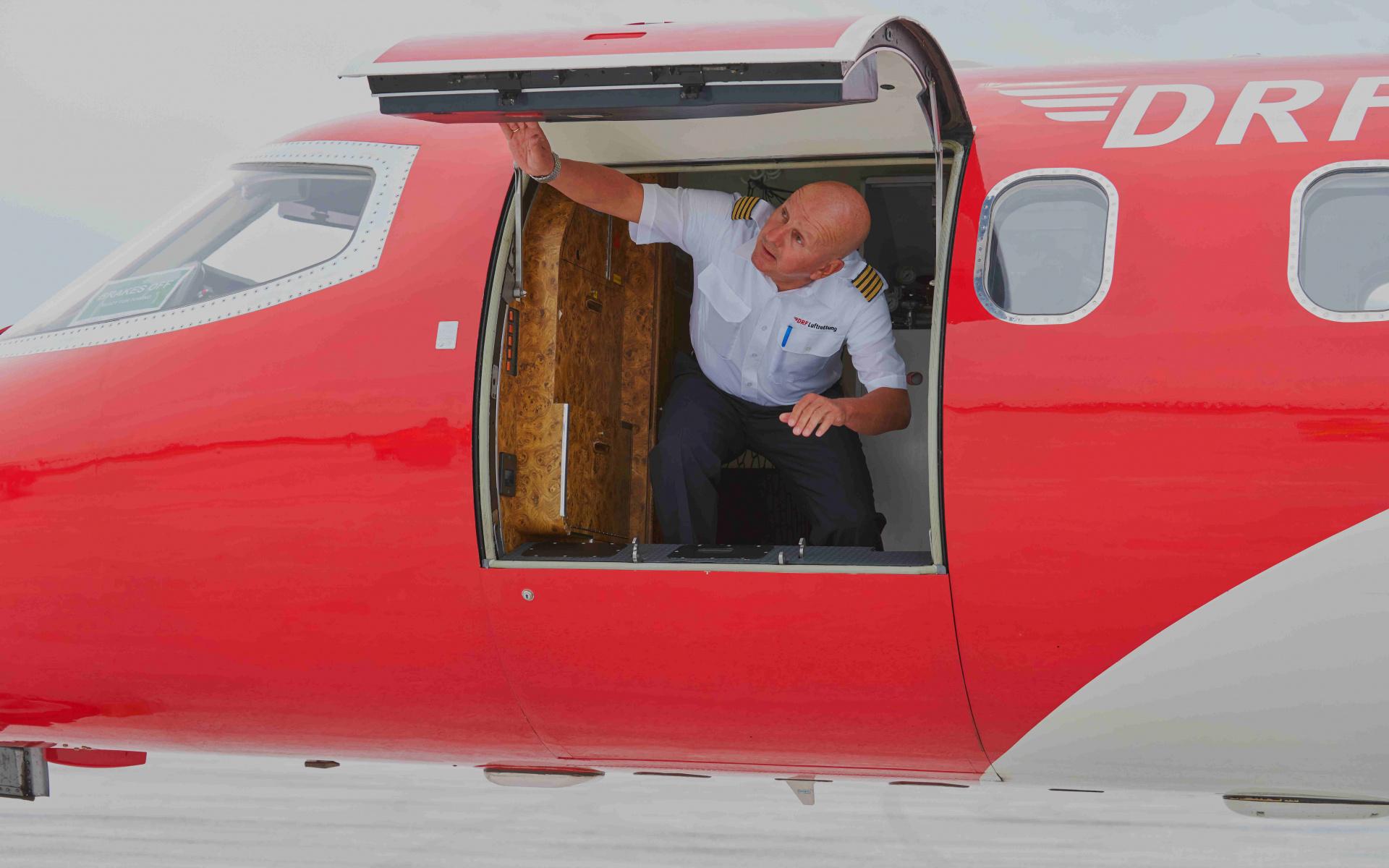 Ein Pilot schaut aus der Türe eines Learjets der DRF Luftrettung.