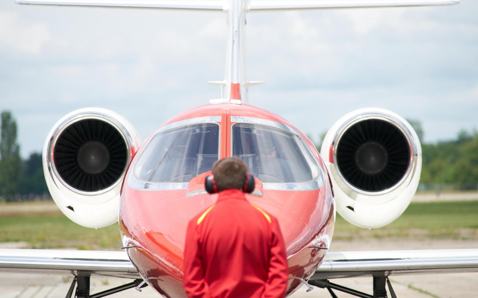 Ein Fluglotse steht vor einem Learjet der DRF Luftrettung.