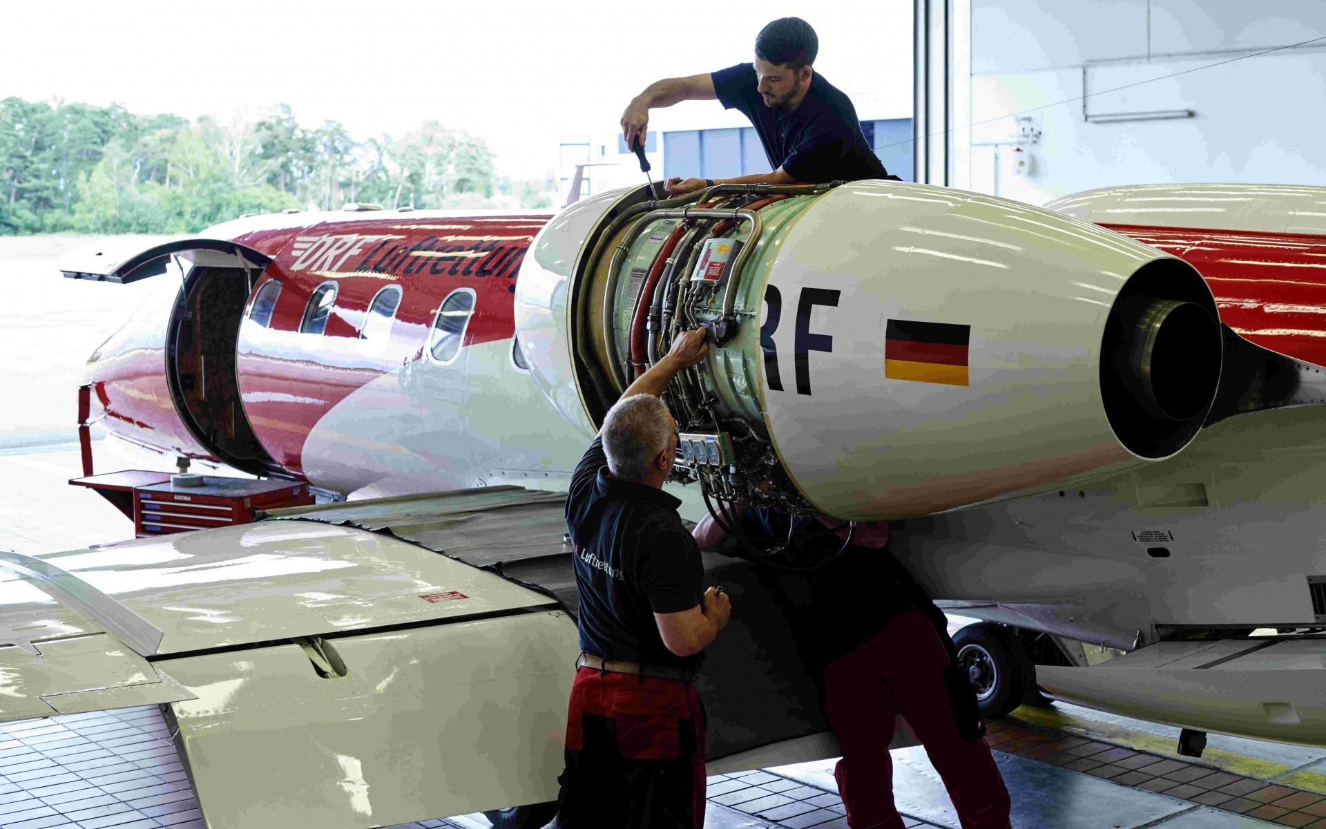 Drei Techniker arbeiten an einem Triebwerk eines Ambulanzflugzeuges der DRF Luftrettung.