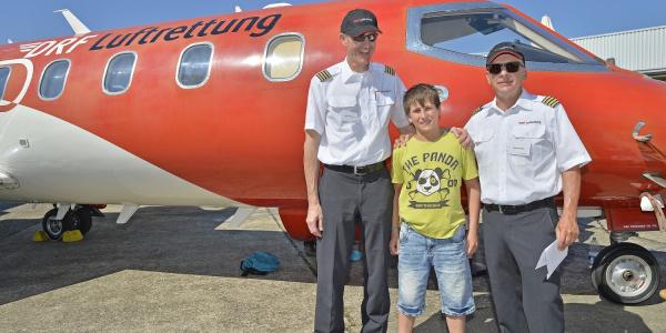 Zwei Piloten und ein Junge stehen vor dem Ambulanzflugzeug der DRF Luftrettung